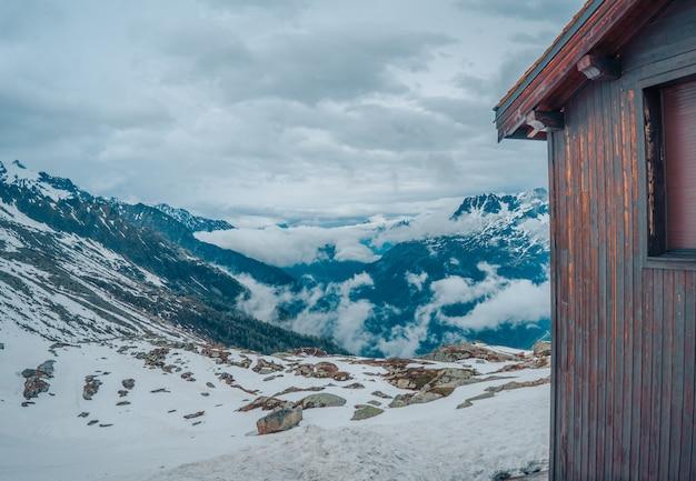 Bello colpo di una casa di legno nelle montagne in inverno con il cielo grigio nei precedenti
