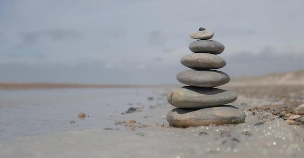Bello colpo di una pila di rocce sulla spiaggia - concetto di stabilità di affari