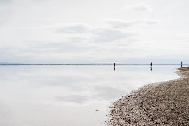 Bello colpo di una spiaggia con tre persone lì in una giornata nuvolosa
