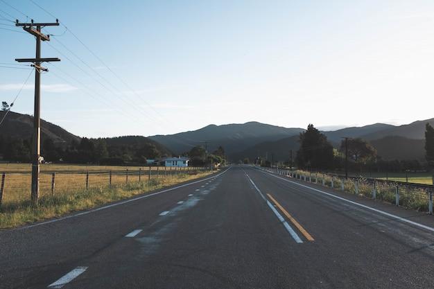 Bello colpo di una strada solitaria vuota grigia nella campagna con le montagne