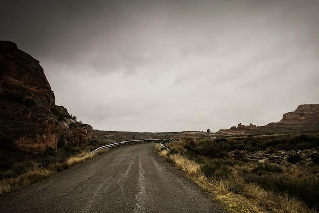 Bello colpo di una strada vuota in mezzo alle rocce e al campo di erba asciutta sotto un cielo nuvoloso