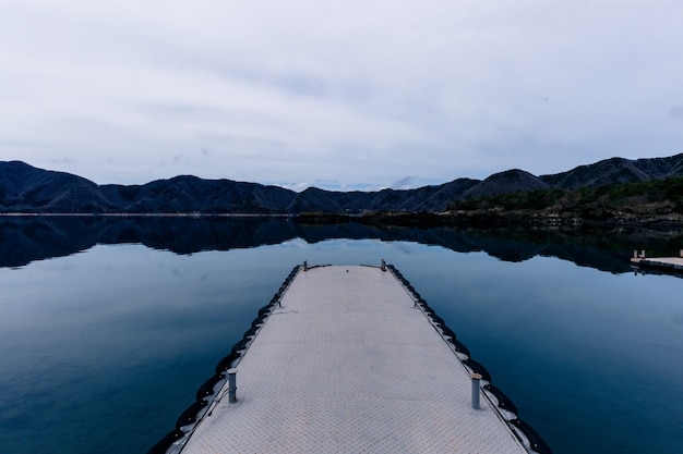 Bello colpo di una via sull'acqua con le montagne nella distanza sotto un cielo nuvoloso