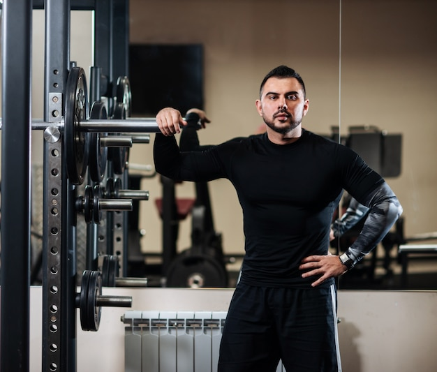 Bello con grandi muscoli in posa accanto al bilanciere