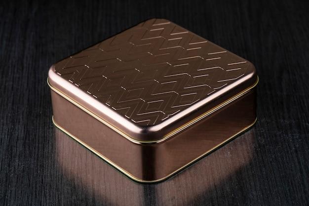 Bello contenitore di metallo dorato su una tavola scura isolata. pacco regalo