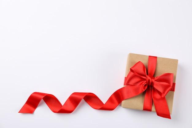 Bello contenitore di regalo con l'arco rosso su fondo bianco, spazio per testo