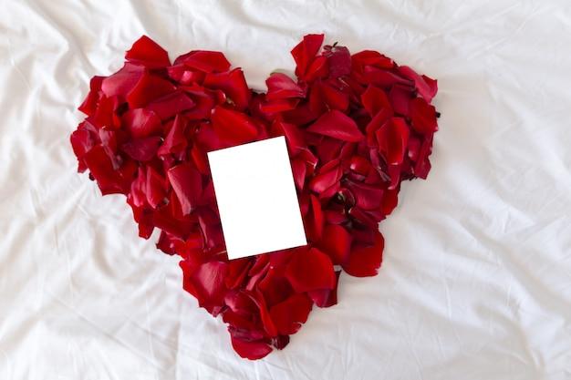 Bello cuore dei petali di rosa rossa con la cartolina d'auguri in bianco per il biglietto di s. valentino