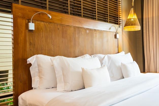 Bello cuscino bianco comodo di lusso sulla decorazione della coperta e del letto in camera da letto
