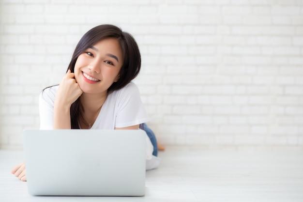 Bello della donna asiatica del ritratto che lavora computer portatile online