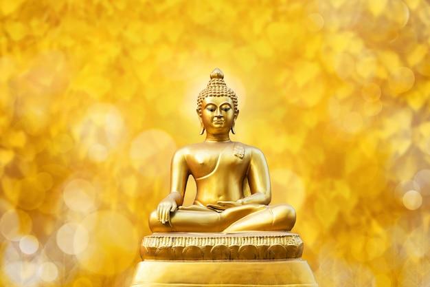 Bello della statua dorata di buddha sulla foglia gialla dorata di pho della foglia del bokeh (foglia di bo).