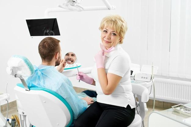 Bello dentista femminile che tiene uno specchio per un cliente maschio di un'odontoiatria che sta sorridendo controllando i suoi denti.