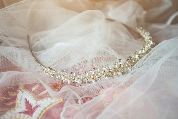 Bello diadema di cristallo sul velo bianco della sposa sulla sedia d'annata nella cerimonia di nozze.