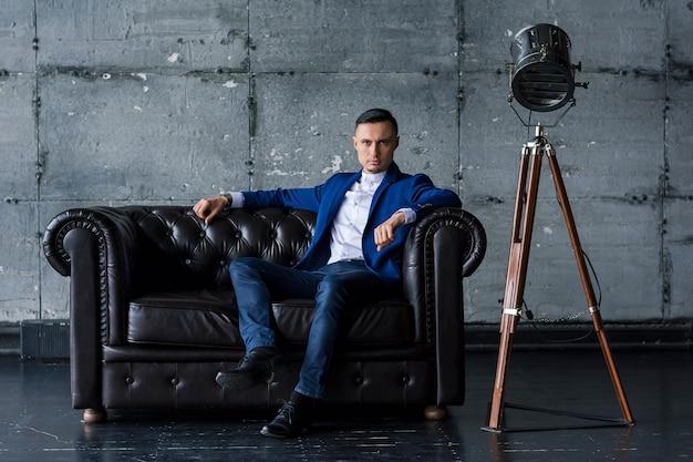 Bello elegante giovane alla moda in una giacca blu si siede su un divano in pelle