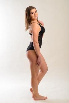 Bello ente grassoccia sexy della donna in studio con i tatuaggi. ritratto in studio femminile, tuta nera