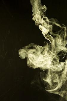 Bello estratto giallo del fumo su fondo nero