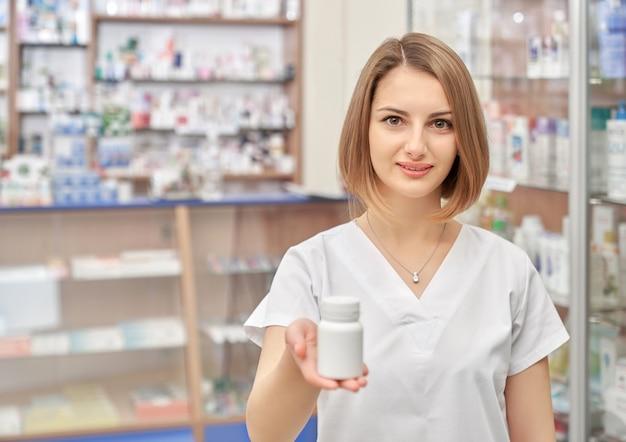 Bello farmacista della donna che posa nella farmacia.