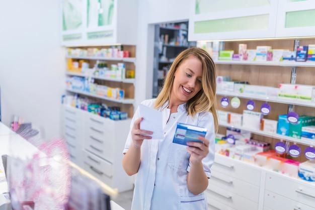 Bello farmacista femminile che lavora in una farmacia con cliente amichevole a
