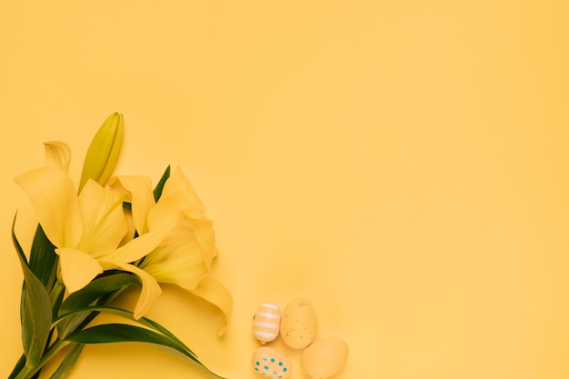 Bello fiore del giglio giallo con le uova di pasqua sul contesto giallo