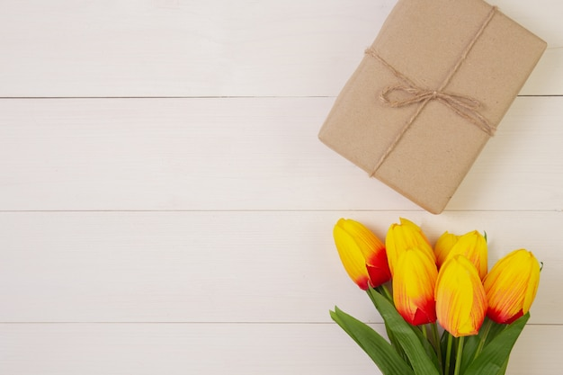 Bello fiore del tulipano e contenitore di regalo su fondo di legno con romantico