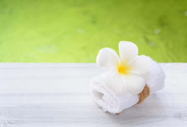 Bello fiore della stazione termale del frangipane con l'asciugamano bianco sulla tavola di legno con il fondo dello stagno di verde della natura