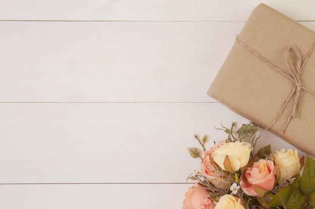 Bello fiore e contenitore di regalo su fondo di legno con romantico