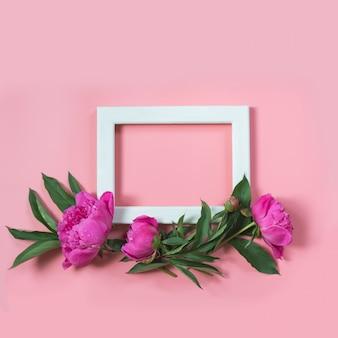 Bello fiore rosa della peonia e struttura bianca per testo sul rosa pastello incisivo. copia spazio. vista dall'alto. disteso.