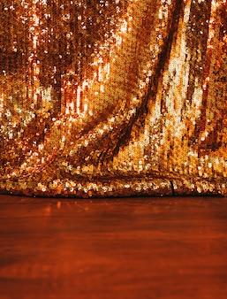 Bello fondo dorato degli zecchini di scintillio su superficie di legno