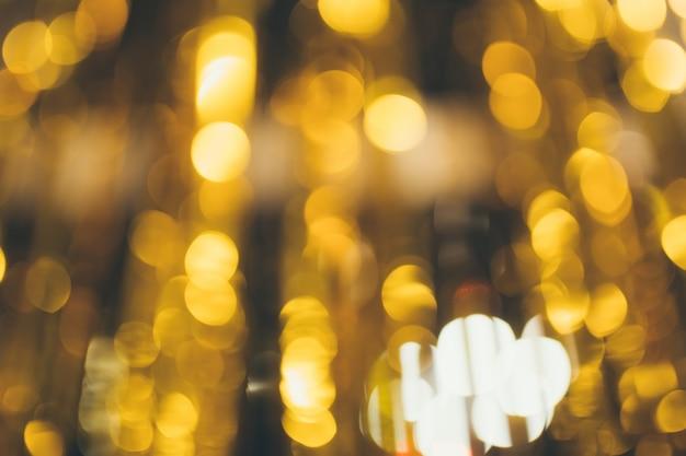 Bello fondo vago dorato del bokeh con lo spazio della copia. trama di vacanza sfondo. punti luce scintillio su sfondo dorato, sfocato