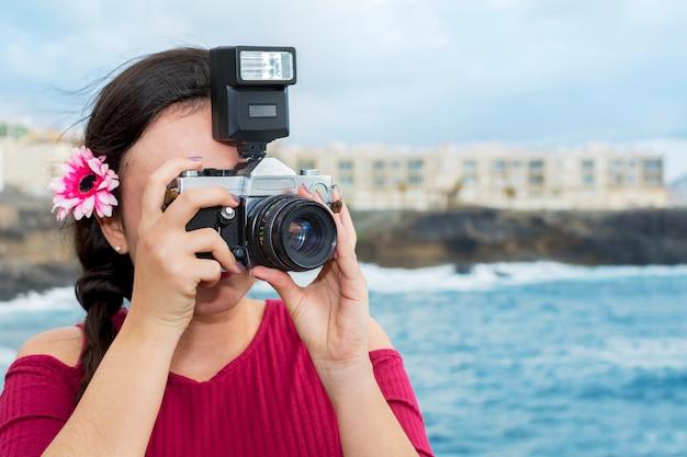 Bello fotografo che fa un giro turistico vicino al mare