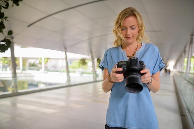 Bello fotografo turistico biondo della donna che usando macchina fotografica all'aperto