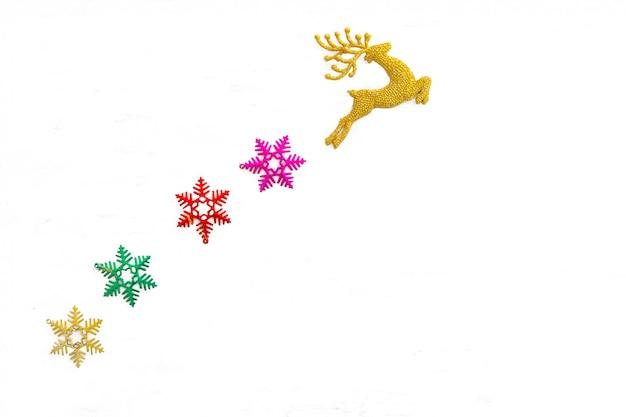 Bello giocattolo dorato della renna e fiocchi della neve isolati su bianco, decorazione dell'albero di natale