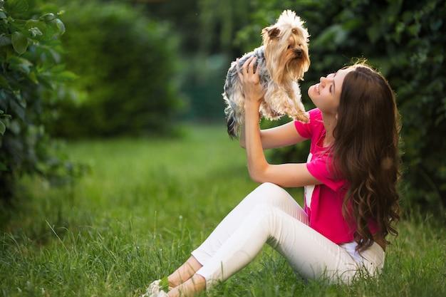 Bello gioco della donna con il cane che si siede sull'erba nel parco verde.