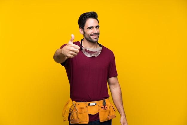 Bello giovane artigiano sopra giallo isolato con il pollice in alto perché è successo qualcosa di buono