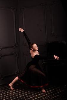 Bello giovane ballerino di balletto classico femminile sulle scarpe da punta che indossano un body e una gonna neri su un mattone