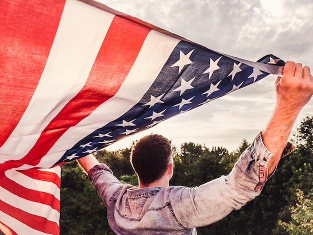 Bello, giovane che tiene una bandiera americana