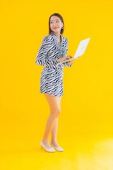Bello giovane computer portatile asiatico di uso della donna del ritratto su giallo