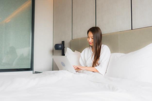 Bello giovane computer portatile o computer asiatico di uso della donna del ritratto in camera da letto