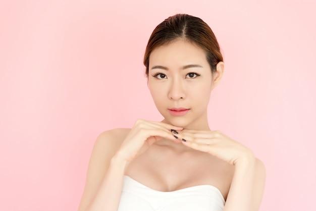 Bello giovane fronte asiatico della donna del primo piano isolato sul rosa