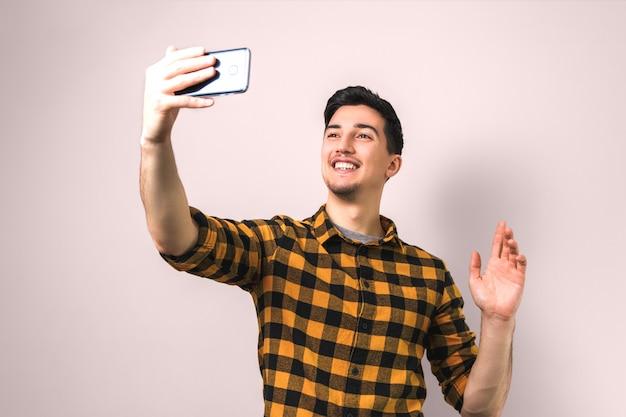 Bello giovane in camicia gialla casual in chat video tramite smartphone