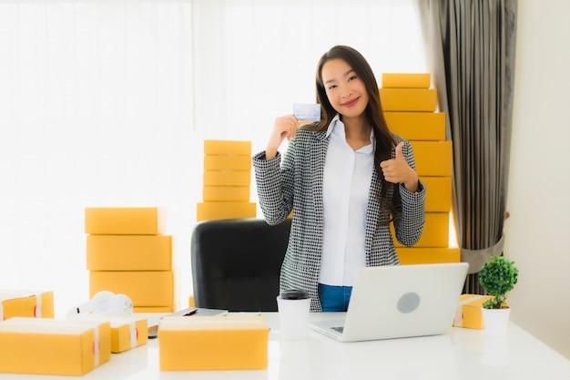 Bello giovane lavoro asiatico della donna del ritratto dalla casa con la carta di credito e la scatola di cartone pronte per la spedizione di acquisto