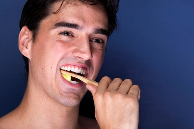 Bello giovane maschio che pulisce i suoi denti