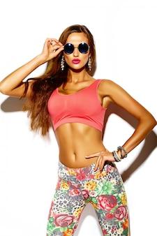 Bello giovane modello sorridente sexy alla moda di sport di fascino pazzo divertente bello in vestiti luminosi dei pantaloni a vita bassa di estate con le grandi tette