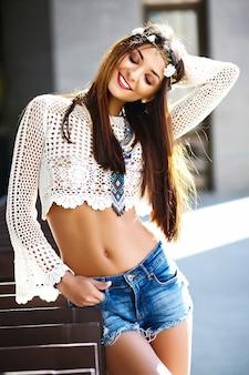 Bello giovane modello sorridente sexy sexy alla moda divertente della donna del hippy in vestiti freschi bianchi dei pantaloni a vita bassa di estate nella via