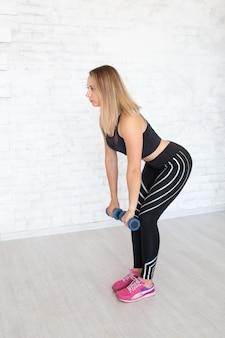 Bello giovane modello sportivo fitness con manubri