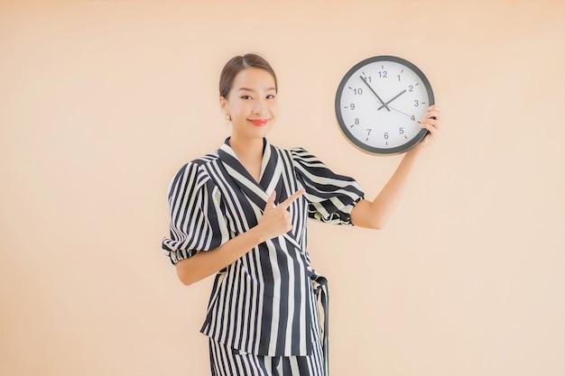 Bello giovane orologio o allarme asiatico di manifestazione della donna del ritratto