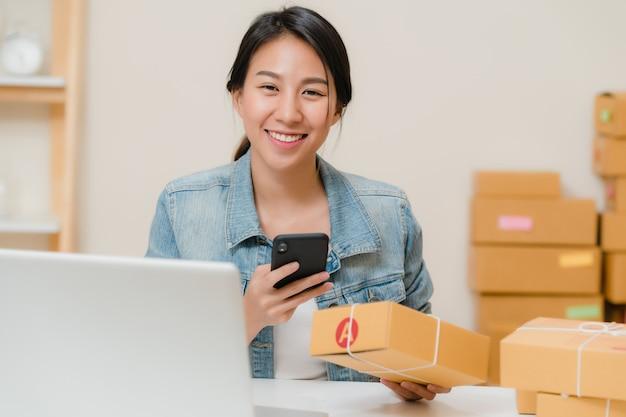 Bello giovane proprietario di donna asiatico astuto di affari dell'imprenditore della pmi che controlla prodotto sul codice di qr di ricerca di riserva che lavora a casa.