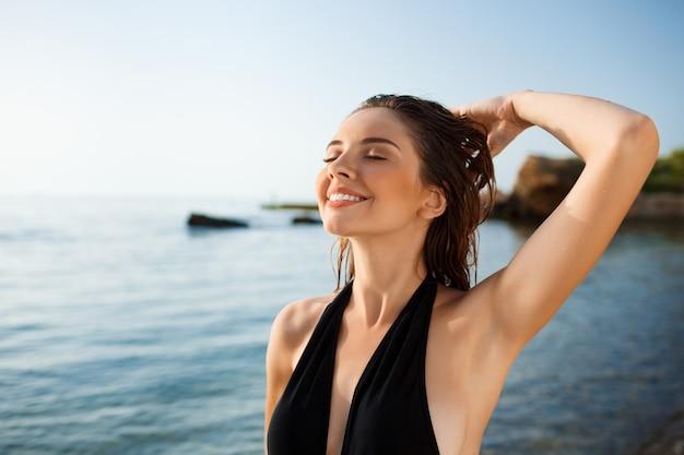 Bello giovane resto allegro della ragazza alla spiaggia di mattina