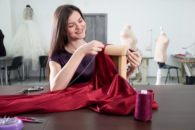 Bello giovane sarto da donna in laboratorio che cuce vestito rosso nello studio del sarto