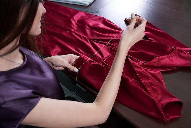 Bello giovane sarto da donna in laboratorio che cuce vestito rosso
