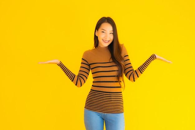 Bello giovane sorriso asiatico della donna adulta del ritratto con molta azione sulla parete gialla