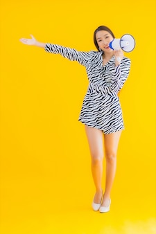 Bello giovane sorriso asiatico della donna del ritratto soddisfatto del megafono su giallo